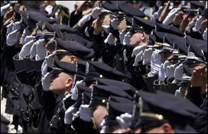 Police officers salute during a memorial service for fallen Massachusetts Institute of Technology campus officer Sean Collier at MIT in Cambridge, Mass.
