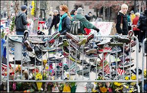 Running shoes hang from a barrier at a makeshift memorial in Copley Square in Boston, which reopened on Wednesday for the first time since the two bombings during the marathon on April 15.