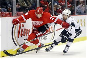 The Red Wings' Damien Brunner, left, battles the Kings' Jarret Stoll for the puck. The Wings picked up two key points with a 3-1 win.