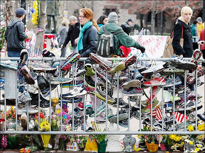 Boston Marathon running shoes Running shoes hang from a barrier at a makeshift memorial in Copley Square in Boston, which reopened on Wednesday for the first time since the two bombings during the marathon on April 15.