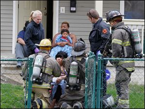 Toledo fire and rescue personnel attend to an Kizzie Smith, a neighbor of the house in the 1400 block of Huron Street, that collapsed.