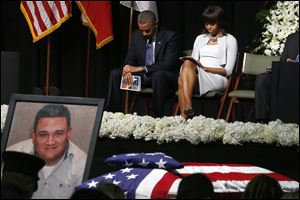 President Obama and first lady Michelle Obama bow their heads behind a photo of volunteer firefighter Capt. Cyrus Adam Reed, who was killed, as they attend the memorial for victims of the fertilizer plant explosion in West, Texas.
