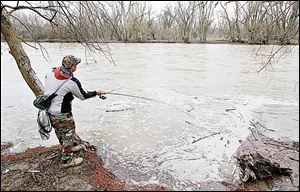 Andy Borton of Wauseon fishes the Maumee River at Side Cut Metropark in Maumee. Swift currents make wading treacherous; debris interferes near shore.