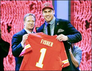 Central Michigan offensive tackle Eric Fisher holds his jersey along with NFL commissioner Roger Goodell after being selected first overall by the Kansas City Chiefs in NFL draft.