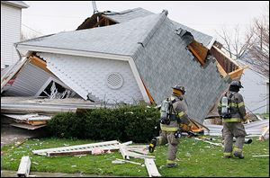 Toledo police and firefighters examine a house at 1448 N. Huron St. that collapsed after a large explosion Thursday.