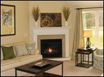 A vaulted ceiling and a gas fireplace with a granite surround make this great room an inviting space.