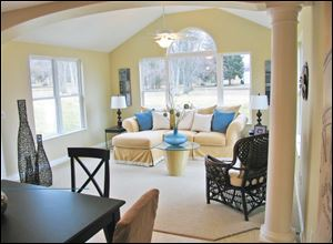 An archway supported by pillars defines the opening to this delightful sunroom.