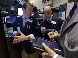 In this Tuesday, April 16, 2013, photo, Specialist Michael O'Mara, left, and trader Fred Demarco work on the floor of the New York Stock Exchange. World stock markets fell today after Japan faced an unwelcome drop in consumer prices.