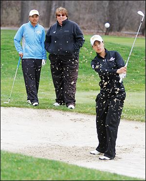 UT golfer Sathika Ruenreong, left, and coach Nicole Hollingsworth watch Manisa Isavas practice recently at the Toledo Country Club. Ruenreong fired a 77 and Isavas a 78 at Friday's MAC tournament.