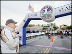 Tom Falvey holds a U.S. flag as the national anthem is played before the start of the 2012 Glass City Marathon.