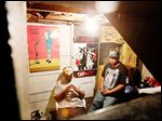 Aaron Belton, left, and his brother Christopher Belton sit in their basement recording studio where Christopher composes music for his group Flip Cash.