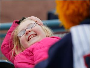 Victoria Lang, 8, North Baltimore, laughs as she's playfully teased by Muddy the Mud Hen as the Toledo Mud Hens play the Columbus Clippers at Fifth Third Field.
