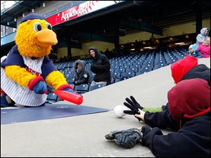 Muddy the Mud Hen shoots a ball to young fans as the Toledo Mud Hens play the Columbus Clippers at Fifth Third Field.