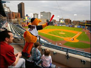 Muddy the Mud Hen cheers his team to the amusement of Dustin Macaulay, Toledo, and his children Alex Macaulay, 7, and Brooklyn Macaulay, 5, as the Toledo Mud Hens play the Columbus Clippers at Fifth Third Field.