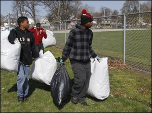 Ckalvin Smith, 14, left, and Devon Lewis, right, both 14, carry bags of leaves and trash to the dumpster.