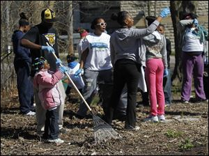 Walter Grier III helps his daughter Whitney, a kindergartner at Robinson Junior High School clean up around her school.