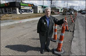 Mike Saine, manager of Batteries Plus store, stands amidst the Secor Road construction in front of his shop on April 24, 2013.