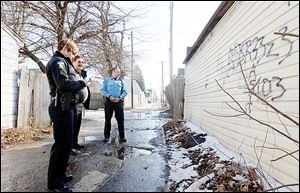 Toledo Police Officers Denise Fischer, left, and J.C. Eischen, right, speak with David Corns, a homeowner in the 600 block of East Broadway who had alerted  authorities to the gang-related graffiti on the back of his garage.
