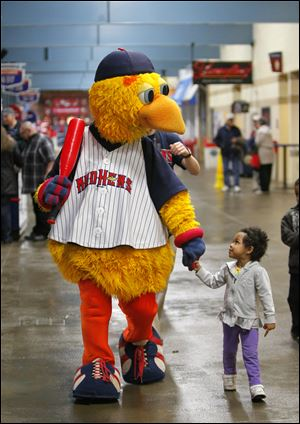Muddy the Mud Hen walks with Myschell Gaitor, 3, along the concourse at Fifth Third Field.