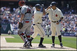 Detroit Tigers' Jhonny Peralta is congratulated by teammate Victor Martinez behind Atlanta Braves catcher Evan Gattis after they both scored on Peralta's two-run home run in the second inning Saturday in Detroit.