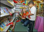 PTA President Kate Schmus helps kindergartner Ireese Vinson, 6, choose books at Temperance Road Elementary's book fair. The building is to close at the end of  this school year.