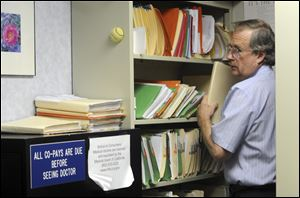 Ted Hole files papers, answers calls, makes appointments, and check in his patients among other duties. The 63-year old doctor has been in practice alone for 34 years.
