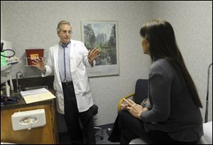 Dr. Ted Hole talks with his patient Cruz Hansen about her allergies.