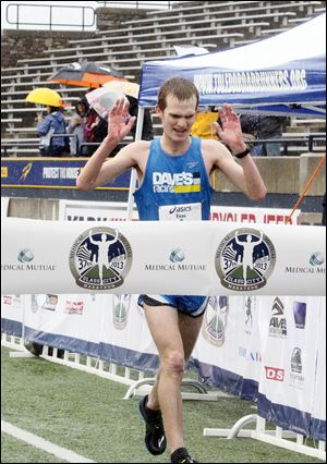 Evan Gaynor of Delta set a course record of 2 hours, 21 minutes, 20 seconds to win the men's title at the Medical Mutual Glass City Marathon.