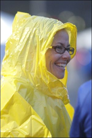 Carrie Zimmerman, from Bryan, Ohio, wears a yellow raincoat and a smile as she prepares to start the race.