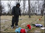 Mitchell Moore, an ex-gang member, stands at the grave site of his son Montrese Moore, a member of the Manor Boyz who died last year at the age of 19 in a shooting at the corner of Cherry and Bancroft streets.