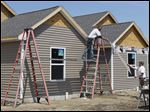 Jeffrey Hughes Construction workers Cory Notman, left, and Joe Metzler install siding on the Kensington Gardens Apartments at 8375 Waterville-Monclova Rd. in Waterville.