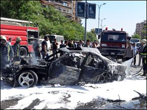 Syrian fire fighters extinguish burning cars after a car bomb exploded in the capital's western neighborhood of Mazzeh, in Damascus, Syria, today.