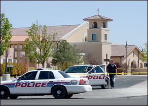 An Albuquerque Police officer walks behind the tape at St. Jude Thaddeus Catholic Church, Sunday in Albuquerque, N.M., the scene of a multiple stabbing at the conclusion of morning services.