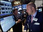 Specialist John Parisi, right, works at his post on the floor of the New York Stock Exchange Tuesday, April 30, 2013. Stock prices are opening mostly lower on Wall Street as weak earnings from Pfizer and other companies drag down major market averages. (AP Photo/Richard Drew)