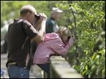 Jerry Gardella, left, and his daughter Emma Gardella, both of Sheffield Lake, look on during last year's The Biggest Week in American Birding event along the boardwalk in the Magee Marsh in Oak Harbor.