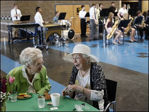 Jane Blair, 93, left, and Martha Vail, 92, right, laugh together as they eat dessert and listen to music played by Perrysburg High School students.