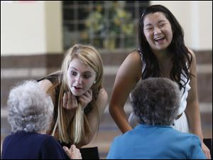 Abby Loehrke, 16, left, and Eva Weigman, 16, right, laugh with two senior citizens while serving dinner.