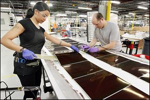 Jasmine James, left, and Jonathan Smith, right, work on solar panels at Xunlight Corp.
