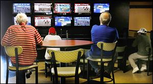 Horse racing fans watch both harness and thoroughbred races on simulcast at Raceway Park on Wednesday. Live racing is held on Saturdays and Sundays.