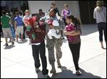 Sgt. Renata Morgan, of North Toledo, center, talks with her son Kelvin Gist, Jr., 11, left, and niece Ja'Lycia Price, 9, right, Thursday afternoon at the conclusion of the welcome home ceremony held for the 323rd Military Police Company at Cedar Creek Church in Perrysburg.