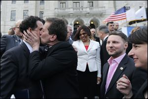 Rhode Island House Speaker Gordon Fox, left, is kissed by R.I. Rep. Frank Ferri, D-Warwick, after a gay marriage bill was signed into law outside the State House in Providence, R.I.