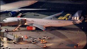 In this image taken from video and provided by television station WNBC-TV, a damaged SAS Airbus A330 sits on the tarmac at Newark Liberty International Airport after clipping the wing of another aircraft on takeoff.