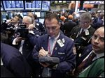 Traders gather at a post on the floor of the New York Stock Exchange.