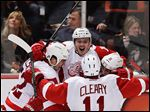 Red Wings center Gustav Nyquist, top, celebrates his winning goal with Jonathan Ericsson, left, Daniel Cleary, and Valtteri Filppula against the Anaheim Ducks during overtime in Game 2 on Thursday night. The series is now tied at a game apiece.