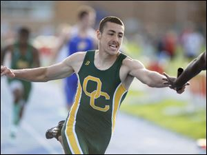Oregon Clay's Carlos Saenz, left, hands off to teammate Israel Jeanlouis during the 4x200 meter relay.
