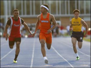 Sylvania Southview High School's Malcolm Johnson, center, wins the 100 meter dash ahead of Central Catholic's Aaron Taylor, left, and Toledo Christian's Tylor Miller, right,  during the Knight Relays at St. Francis de Sales High School.