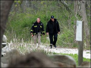 Massachusetts State Police walk out of the woods of the Smith Neck Farm in Dartmouth, Mass. as federal, state and local authorities on Friday searched the woods near the UMass-Dartmouth campus as part of the Boston bombing investigation.