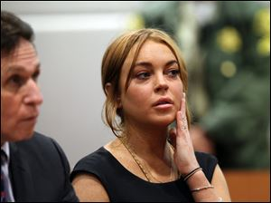 Actress Lindsay Lohan appears in Los Angeles court with her new attorney Mark Heller, left, for a pretrial hearing, Wednesday, Jan. 30, 2013, in a case filed over the actress' June car crash.