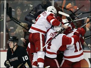 Detroit Red Wings players celebrate Gustav Nyquist's goal during overtime as Anaheim Ducks' Corey Perry (10) skates off in Game 2 of their first-round NHL hockey Stanley Cup playoff series.