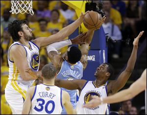 Golden State Warriors' Andrew Bogut, top left, blocks a shot by Denver Nuggets' Andre Iguodala, center, as Warriors' Harrison Barnes, right, watches during the first half of Game 6.